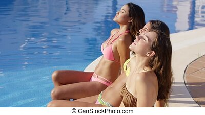 Three sun loving young women in bikinis relaxing at the side...