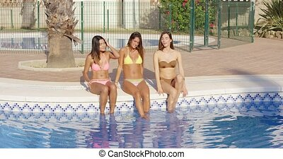 Three happy women sitting on the side of a pool - Three...