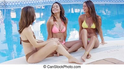 Three sexy young women relaxing chatting poolside in their...