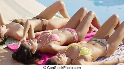 Three sexy shapely young women sunbathing together poolside...