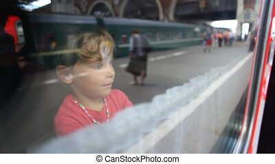 little girl straightening curtains on the train window