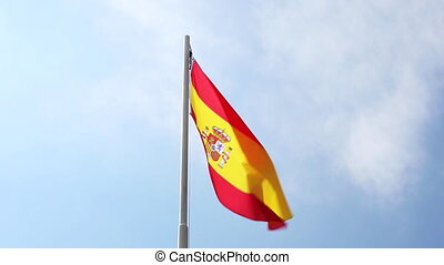 National flag of Spain on a flagpole in front of blue sky