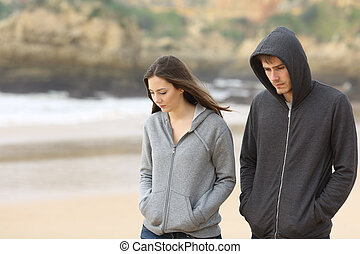 Couple of teenagers walking sad - Couple of angry and sad...