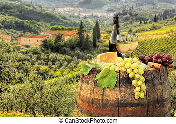 White wine with barrel on famous vineyard in Chianti,...