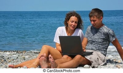 happy man and woman with notebook sitting in rocky beach