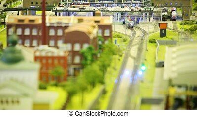 in small model sity trian goes from station on rail near to factory and church