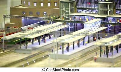 in modern toy city passenger train passes by rail through...