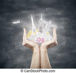 Hands holding traveling sketch on chalkboard background