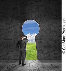 Businessperson looking through keyhole