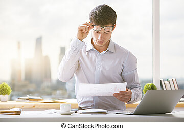 Attractive young businessman doing paperwork - Portrait of...