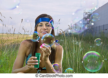 woman blows soap bubbles - beauty young woman blowing soap...