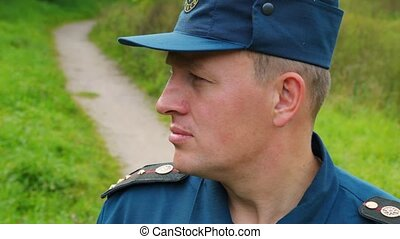 portrait of officer of rescue service standing in park, profile