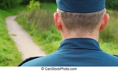 officer in uniform standing back on footpath