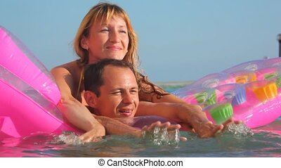 woman and man embracing on inflatable mattress in swimming pool