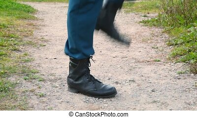 soldier in military boots march on the spot, close up, profile