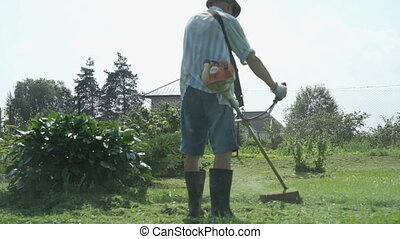Gardener cuts the grass with lawn string trimmer - The...
