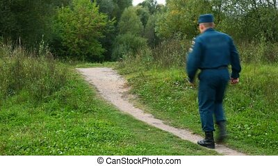 officer of rescue service walking on footpath in park from...