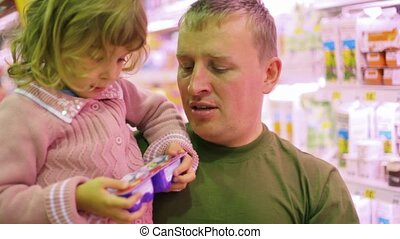 man with little girl buying yogurt in supermarket