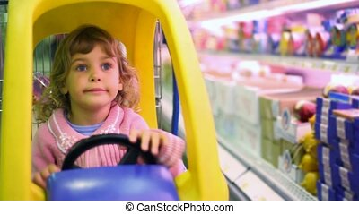 little girl sitting in car-shopping trolley in supermarket