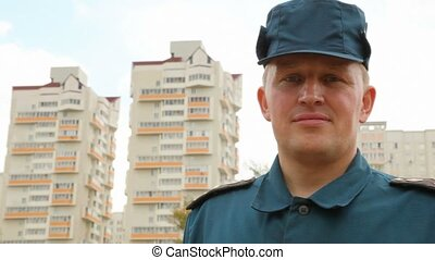 portrait of officer of rescue service standing against housing estate