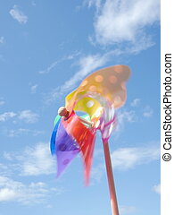 pinwheel - Colorful pinwheel against blue sky with clouds