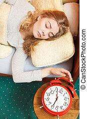 Woman waking up turning off alarm clock in morning -...