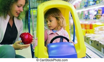 mother speaking with daughter in supermarket