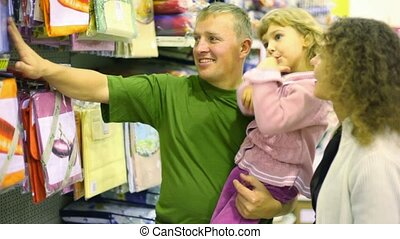 family with little girl buying bedding in supermarket