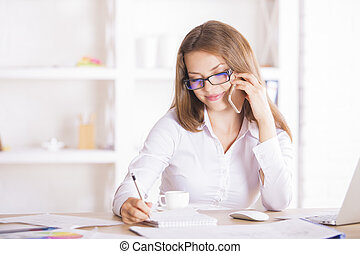 Woman on phone doing paperwork - Attractive smiling woman...