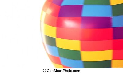 part of coloured toy air ball revolves fast on white...