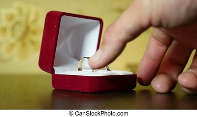 video in her hand wedding rings in red box