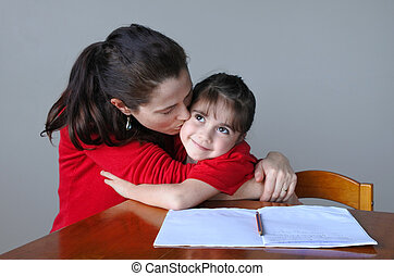 Mother helping her daughter with her school project - Mother...