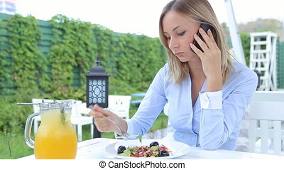 Young, pretty woman talking on cellphone, eating salad in cafe