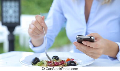 Beautiful woman using smartphone and eating salad in cafe in...