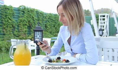 Happy young woman with smartphone in cafe