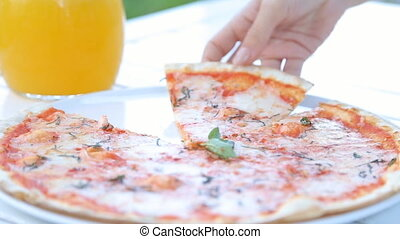 Woman hand take a pieces of pizza.