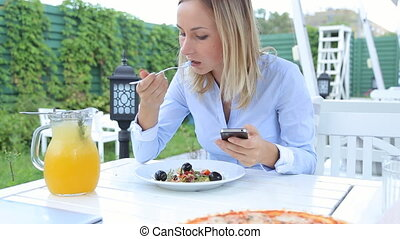 Beautiful woman using smartphone and eating salad in cafe.