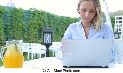Young happy woman with laptop in the cafe