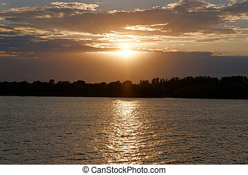 Sunset ove Volga river in Russia. Orange clouds in sunset...