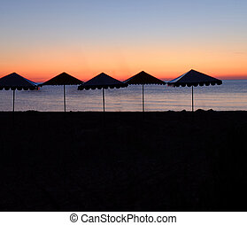 Beach with umbrellas silhouettes after sunset evening...