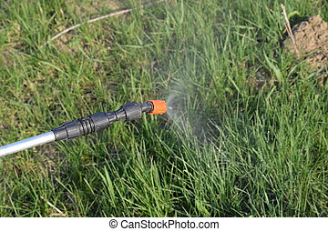 Spraying herbicide from the nozzle of the sprayer manual....