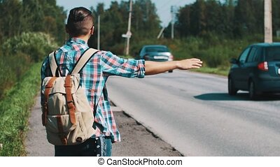 Back side young boy with backpack hitchhiking at road in summer sunny day. Thumb