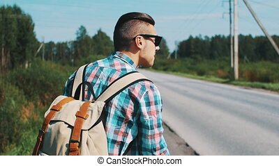 Back side of boy with backpack in sunglasses hitchhiking at road in summer day.