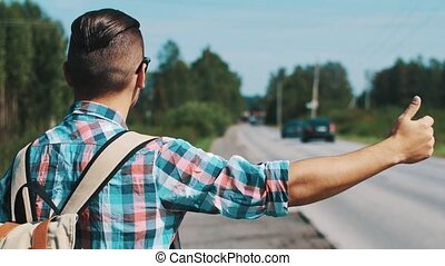 Back side of boy with backpack hitchhiking at road in summer sunny day. Thumb up