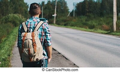 Back side young boy with backpack hitchhiking at road in summer sunny day. Hand
