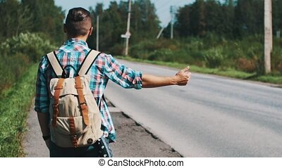 Back side of young boy with backpack hitchhiking at road in summer sunny day.