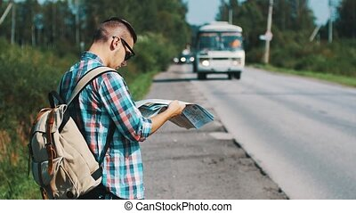 Young boy with map hitchhiking at road in summer sunny day. Tourist. Bus