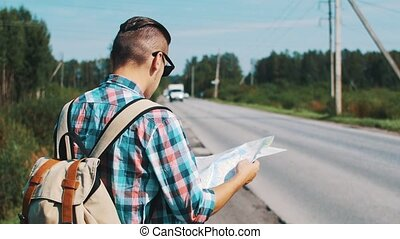 Back side of young boy with map hitchhiking at road in summer sunny day.