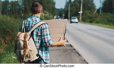 Young boy hitchhiking at road with cardboard plate in summer sunny day. Tourist.