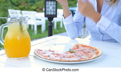 Young couple eating pizza in the restaurant, outdoors